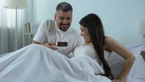 Caring man waking beloved woman giving cake with candle, celebrating anniversary. Stock footage stock video