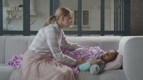Caring mom consoling sleepy sick child on sofa