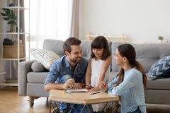Caring mom and dad teaching little daughter to draw. Happy family with kid playing together, caring mom and dad smiling teaching little daughter to draw with stock photo