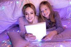 Caring mom and girl lying using their tablet stock photo