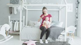 Caring mother brushing baby in children`s room stock video footage