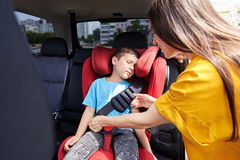 Caring mother checking seat belt sleeping son. Wide shot of caring mother checking seat belt sleeping son Royalty Free Stock Images