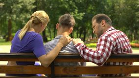 Caring mother and dad supporting sad teen son sitting on bench in park, crisis. Stock footage stock video