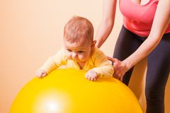 Baby exercises on fitball. Caring mother doing sport exercises with her baby on fitball Stock Photo