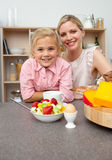 Caring mother eating fruit with her daughter Stock Images