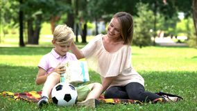 Caring mother giving present box to son, birthday celebration outdoors, surprise stock photography