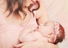 Caring mother holding with love her little cute sleeping baby gi Stock Photo