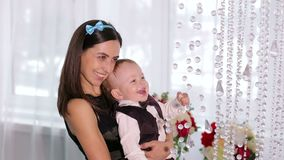 Happy mom plays with her little son in a bright room with beautiful chandelier. A caring mother holds her little son in her arms, the baby is dressed in a stock video footage