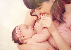 Caring mother kissing fingers of her cute sleeping baby girl. Caring mother kissing little fingers of her cute sleeping baby girl, happy family concept Royalty Free Stock Image