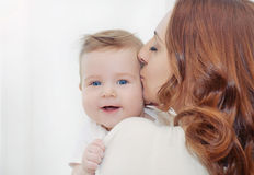 Caring mother kissing  her cute happy baby boy Stock Photos