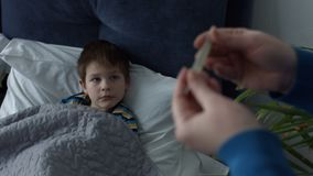 Caring mother measuring temperature of sick boy stock video footage