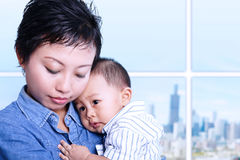 Caring mother nursing baby in office. Caring Asian mother nursing baby in office Royalty Free Stock Photo