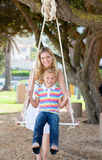 Caring mother pushing her daughter on a swing Stock Images