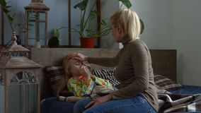Caring mother touching sick daughter`s forehead stock video footage