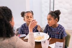 Caring mother wearing pink sweater feeding her cute little girls stock photos
