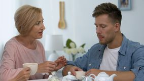 Caring mother wiping lips of son during lunch with girlfriend, shocked situation. Stock footage stock video