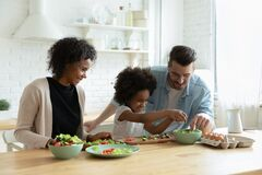 Free Caring Multiethnic Couple Teach Small Daughter Cook Vegetable Salad Stock Images - 186897384