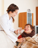 Caring nurse giving glass to   woman Royalty Free Stock Photos