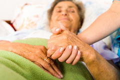 Caring Nurse Holding Hands. Health care nurse holding elderly lady's hand with caring attitude Royalty Free Stock Photo