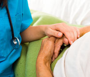 Caring Nurse Holding Hands. Health care nurse holding elderly lady's hand with caring attitude Stock Photography