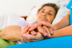 Caring Nurse Holding Hands. Caring nurse holding kind elderly lady's hands in bed Royalty Free Stock Photos