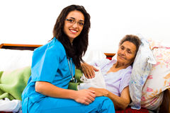 Caring Nurse Holding Hands. Caring nurse holding kind elderly ladys hands in bed royalty free stock images