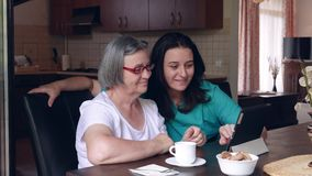 Caring nurse showing a digital tablet to an elderly woman in a nursing home stock footage