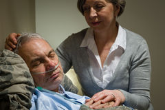 Caring nurse with sleeping senior male patient Royalty Free Stock Images
