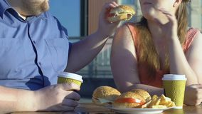 Caring obese man treating his girlfriend burger in outdoor cafe, junk food. Stock footage stock video