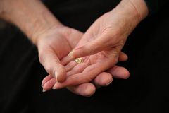 Caring older woman and mans hands. Gentle, graceful, beautiful, married older woman and mans hands holding each other in a caring way on a black background stock images