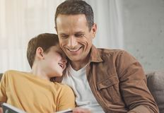 Caring parent reading book for his child. Portrait of happy father reading fairy tale for his lovely son. Boy is leaning head on male shoulder and laughing Stock Photo