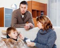 Caring parents giving medicinal sirup to son. Caring parents giving medicinal sirup to teenage son at home royalty free stock photos
