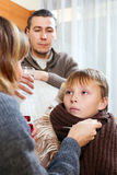 Caring parents giving medicinal sirup to  son. Caring parents giving medicinal sirup to teenage son at home Royalty Free Stock Photos