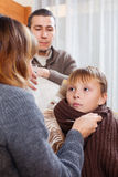 Caring parents giving medicinal sirup to teenage boy. At home stock image