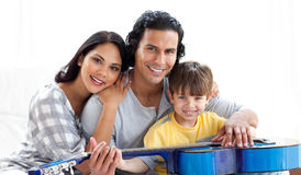 Caring parents playing guitar with their son Stock Image