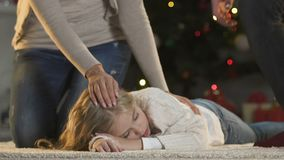 Caring parents stroking little daughter sleeping near X-mas tree cant wait gifts