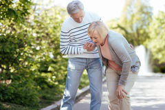 Caring pensioner helping senior wife outdoors. Difficultness of my senior age. Senior loving supportive men caring about his aging wife and helping her while Royalty Free Stock Image
