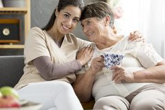 Caring person and elderly woman. Caring person and happy elderly women drinking tea at home Stock Photography