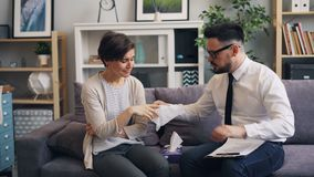 Caring psychologist helping crying woman giving paper tissue touching shoulder. Caring psychologist handsome bearded guy is helping crying woman depressed stock footage