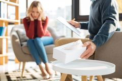 Selective focus of a box with paper tissues. Caring psychologist. Selective focus of a box with paper tissues being taken by a smart male psychologist Royalty Free Stock Images