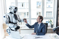 Caring robot is giving espresso to businessman Stock Photos
