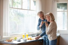 Caring senior husband feed hugging wife at home stock images