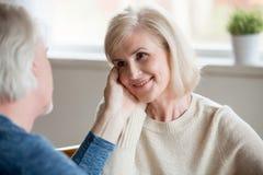 Caring senior husband touching beautiful face of smiling aged wi stock photo