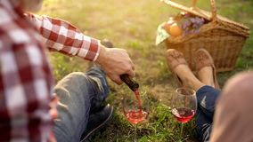 Caring senior man pouring wine in glasses on outdoor date, celebrating holiday royalty free stock photo