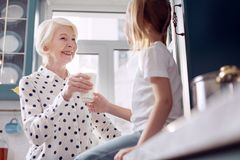 Caring senior woman giving a glass of milk to granddaughter. Healthy lifestyle. Cheerful caring senior women giving a glass of milk to her little daughter and Royalty Free Stock Photos