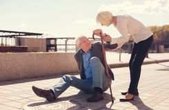Caring senior woman helping her husband get up. Giving support. Petite elderly women holding her husbands arm and helping him to get up from the ground after Stock Photography