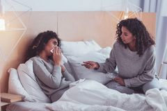 Caring sister taking care of her sick sibling royalty free stock images
