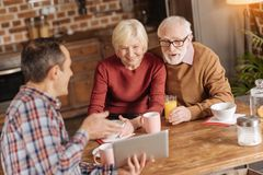Caring son demonstrating video to his senior parents in kitchen. Sharing nice mood. Caring young son showing a funny video to his elderly parents while they Royalty Free Stock Photography
