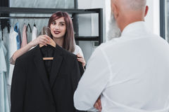 Caring tailor proposing elderly man to try on suit jacket. Caring tailor proposing elderly men to try on suit jacket indoors royalty free stock photo