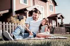 Caring unshaken father sitting and holding monopode. My lovely baby. Caring unshaken handsome father sitting on the ground with his daughter smiling and holding Stock Photos